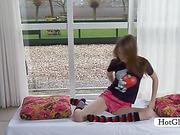 Playful Gloria has fun stripping slowly by the window