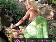 Outdoor solo masturbation scene with curly blonde