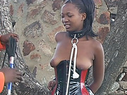 African slut tied up to a tree with leather belts and spanked hard